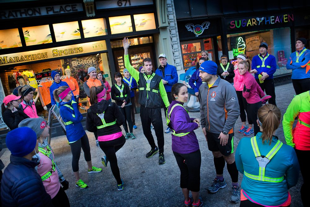 Marathon Sports manager Shane O'Hara gathers members of the store's running group on Boylston Street before they head out on their weekly Wednesday night run.  (Jesse Costa/WBUR)