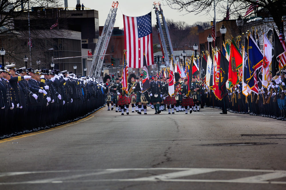 The funeral procession works its way down Main Street in Watertown. (Jesse Costa/WBUR)