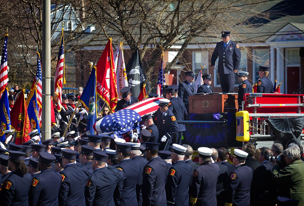 Firefighter Michael Kennedy's casket is carried off a fire truck and toward West Roxbury's Holy Name Church on Thursday. (Jesse Costa/WBUR)