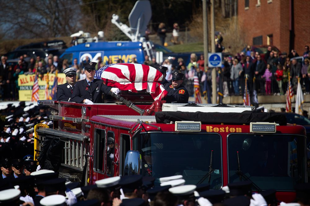 Firefighter Michael Kennedy's casket is brought on Engine 33 to West Roxbury's Holy Name Church on Thursday. (Jesse Costa/WBUR)