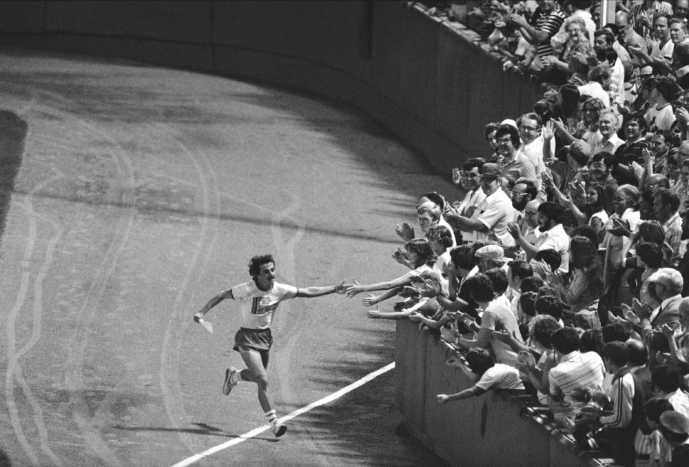 David McGillivray reaches out to excited fans at Fenway Park in Boston on Tuesday, August 29, 1978, as he completes an 80-day cross country run some 3,400 miles to raise cash pledges for children's cancer research. (Maury/AP)