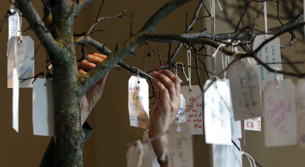 "The anniversary of the Marathon may make people feel as if it's time for closure, but the truth is each person recovers from loss at a different pace. In this photo, a woman hangs a tag on a message tree at an exhibit entitled ""Dear Boston: Messages from the Marathon Memorial"" at the Boston Public Library in Boston, Monday, April 7, 2014. (Elise Amendola/AP)"