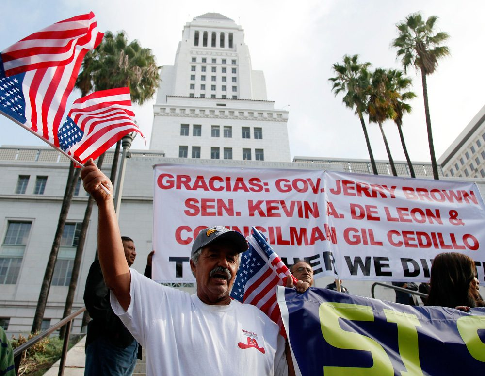 Immigrants celebrate after California's governor signed a bill last year allowing undocumented immigrants to obtain state driver's licenses. A similar bill has been introduced four times in Massachusetts. (Nick Ut/AP)
