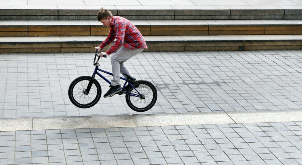 A man rides his bike in downtown Boston on the first day of spring, Thursday, March 20, 2014. (Elise Amendola/AP)