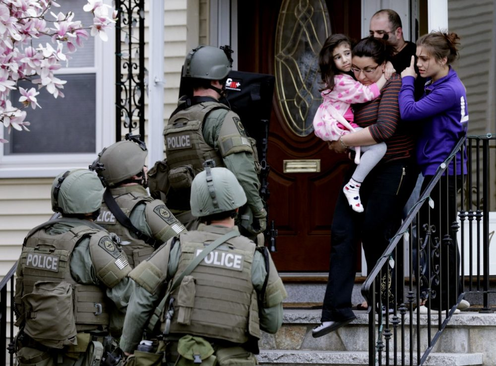 A woman carries a girl from their home as a SWAT team searching for a suspect in the Boston Marathon bombings enters the building in Watertown. (Charles Krupa/AP)