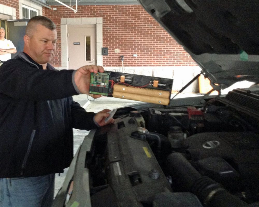 Master Sgt. Kenneth Huddleston, with the federal Department of Homeland Security's mobile training unit, identifies a fake bomb under the hood of a car during a recent training session. (Deborah Becker/WBUR)