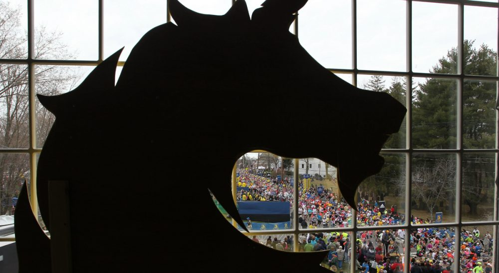 A year has passed since the bombing at the Boston Marathon, but what exactly does that mean? In this photo, behind a silhouette of the Boston Athletic Association logo, runners start the 117th running of the Boston Marathon, in Hopkinton, Mass., Monday, April 15, 2013. (Stew Milne/AP)