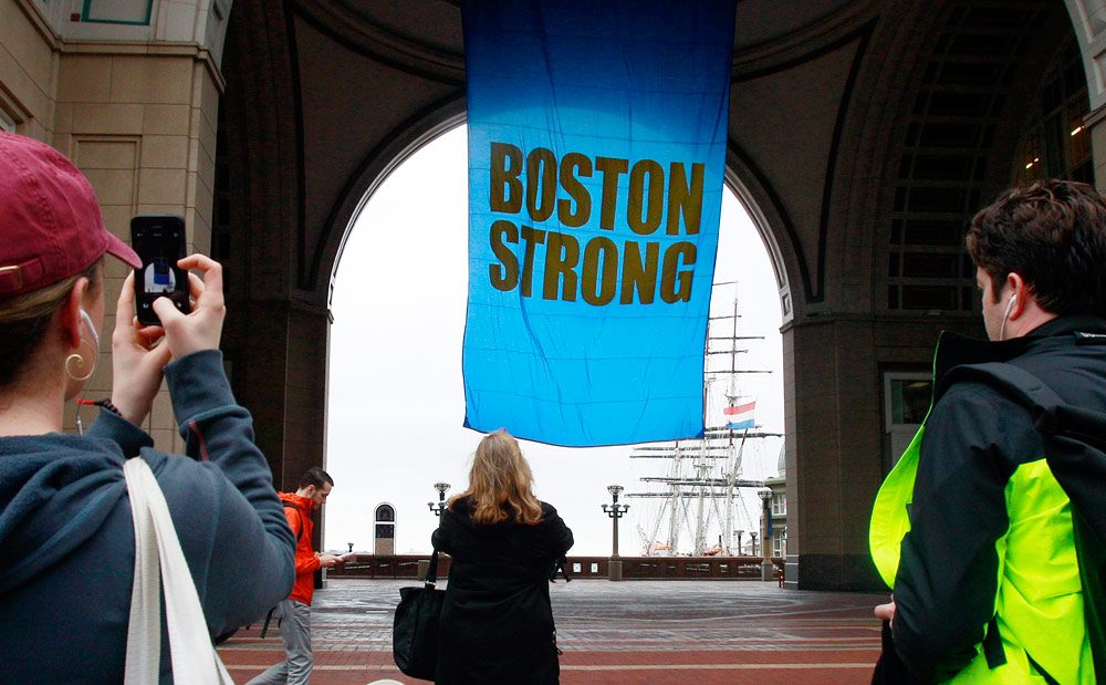 "People photograph a banner reading ""Boston Strong"" at Rowes Wharf, April 15, 2014, in Boston. (AP Photo/Bill Sikes)"
