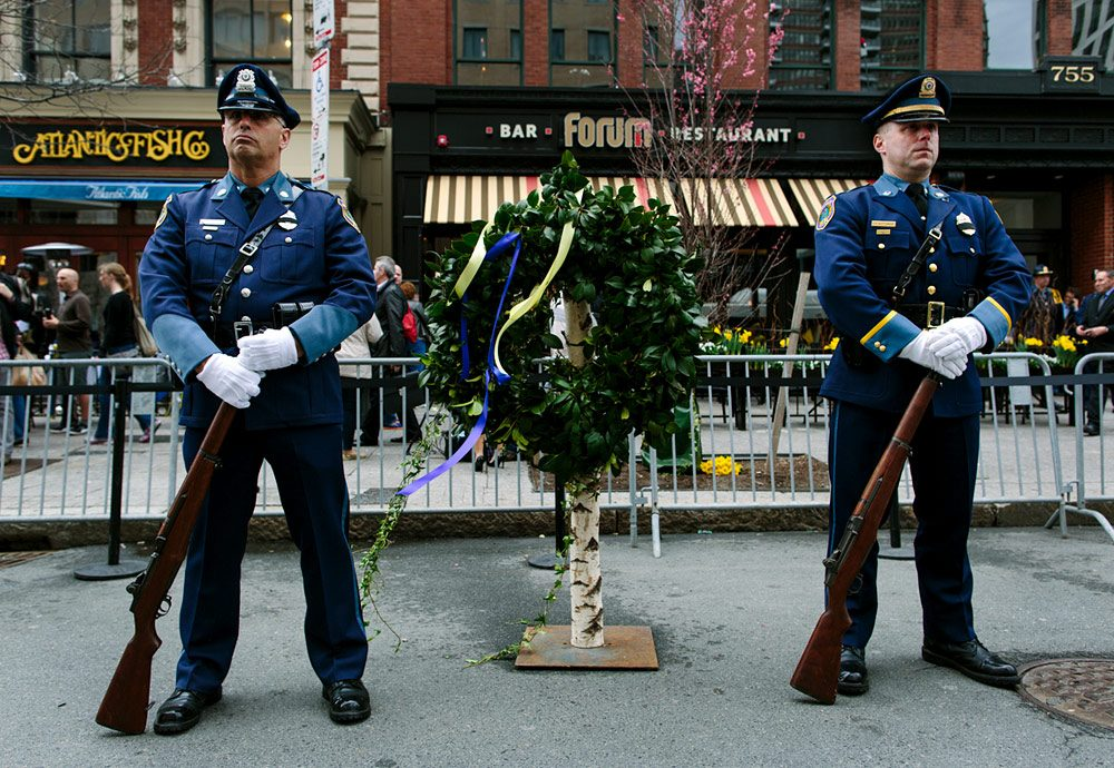 Police honor guard stands with a wreath outside The Forum, the site where the second bomb exploded at last year's Boston Marathon. (Joe Spurr/WBUR)
