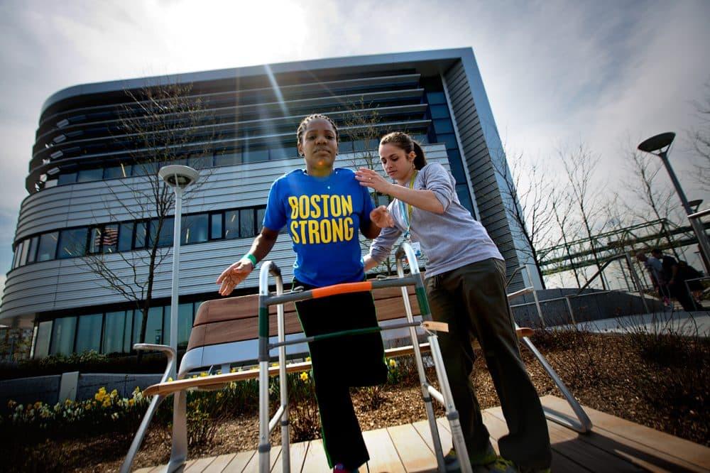 In this 2013 WBUR file photo, marathon bombing survivor Mery Daniel works with occupational therapist Becky Buttiglieri outside the new Spaulding Rehabilitation Hospital. (Jesse Costa/WBUR)