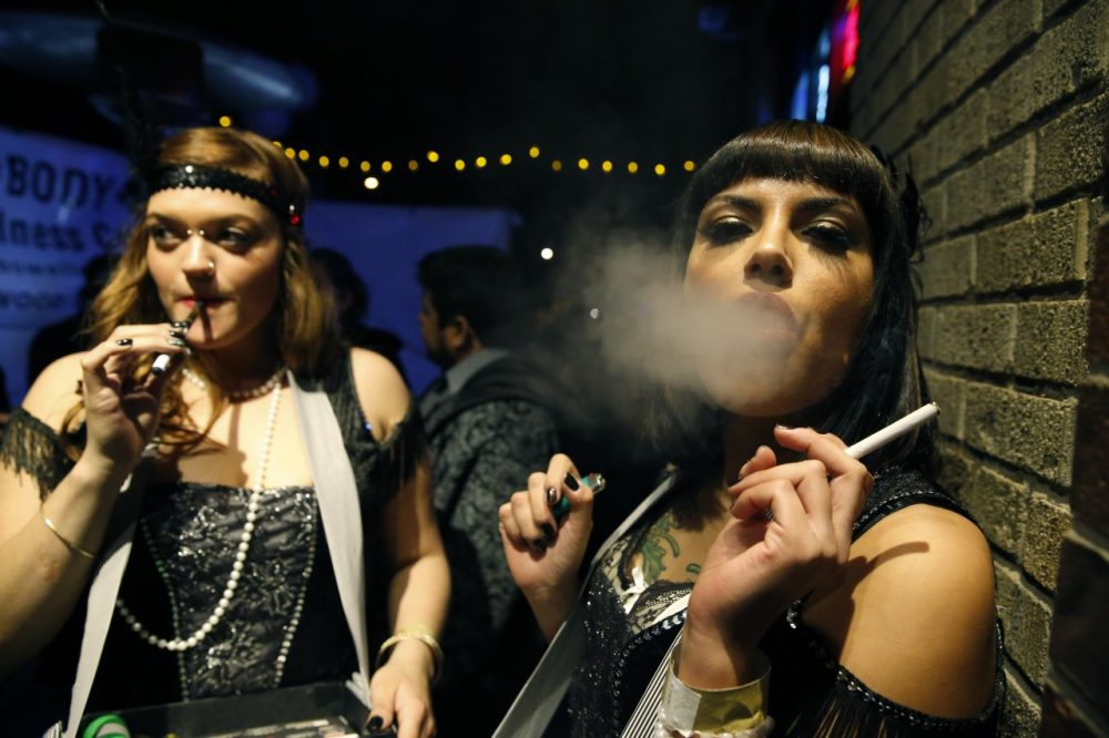 Partygoers smoke marijuana and cigarettes during a Prohibition-era themed New Year's Eve party celebrating the start of retail pot sales, at a bar in Denver. (Brennan Linsley/AP)
