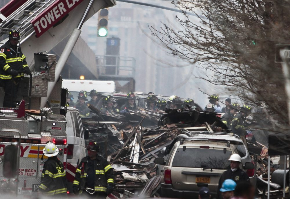 Firefighters continue to investigate and remove debris from an explosion in Harlem, Wednesday, March 12, 2014 in New York. A gas leak triggered an explosion that shattered windows a block away. (Bebeto Matthews/AP)