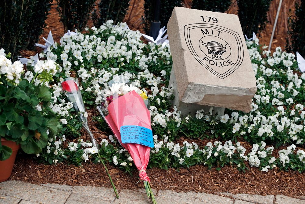 Flowers lay at a memorial stone after a one-year remembrance ceremony for Massachusetts Institute of Technology Officer Sean Collier on campus in Cambridge Friday. (Elise Amendola/AP)