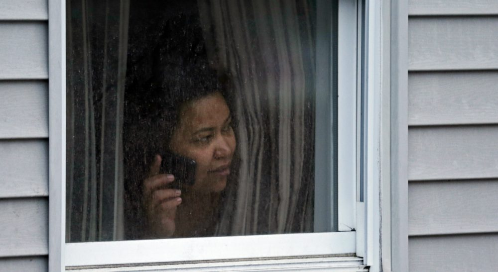 A woman looks out a window at her home as police start to search an apartment building while looking for a suspect in the Boston Marathon bombings in Watertown, Mass., Friday, April 19, 2013. (Charles Krupa/AP)