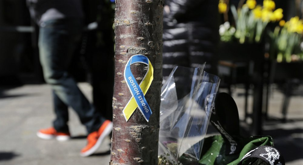 "Social critic Wendy Kaminer says, for better or worse, the Boston Marathon is no longer an athletic event -- it's an icon. In this photo, a patron enters the Forum restaurant, site of one of two bomb blasts during the 2013 Marathon, while passing a ""Boston Strong"" sticker adhered to a tree trunk at a makeshift memorial on Boylston Street. Wednesday, April 16, 2014 in Boston. (Charles Krupa/AP)"