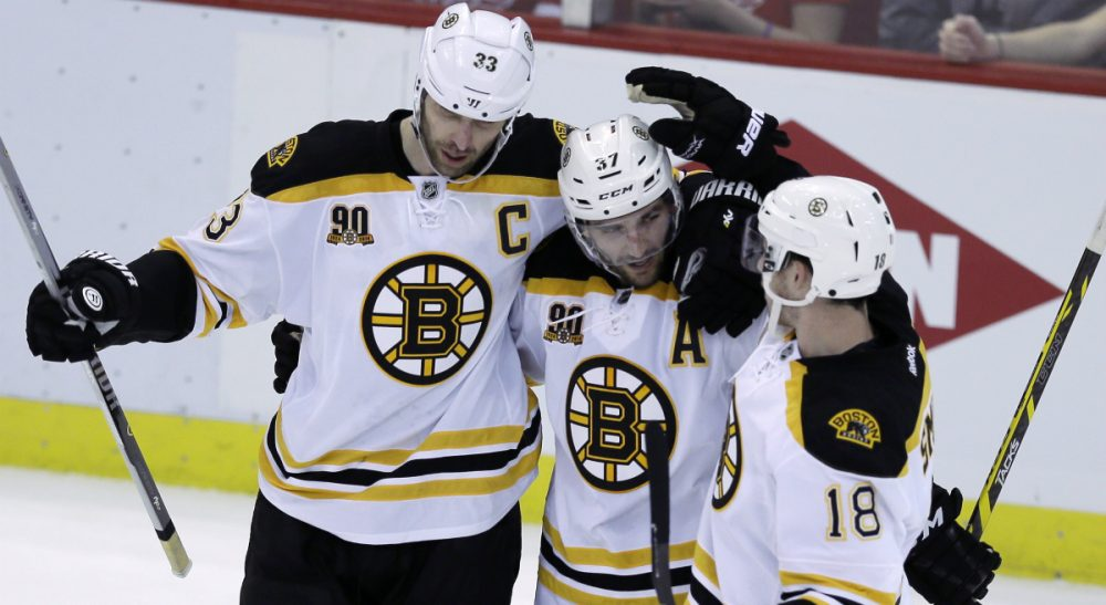 Boston Bruins defenseman Zdeno Chara, left, and right wing Reilly Smith, congratulate center Patrice Bergeron after his empty net goal during the third period of Game 3 of a first-round NHL hockey playoff series against the Detroit Red Wings in Detroit, Tuesday, April 22, 2014. (Carlos Osorio/AP)