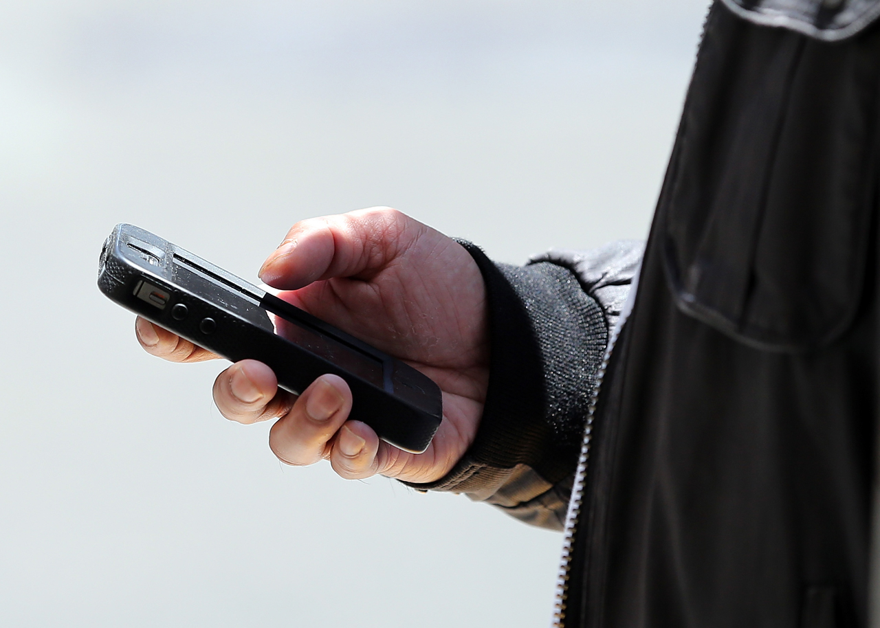 A pedestrian uses a smartphone as he walks along Market Street on June 5, 2013 in San Francisco, California. (Justin Sullivan/Getty Images)