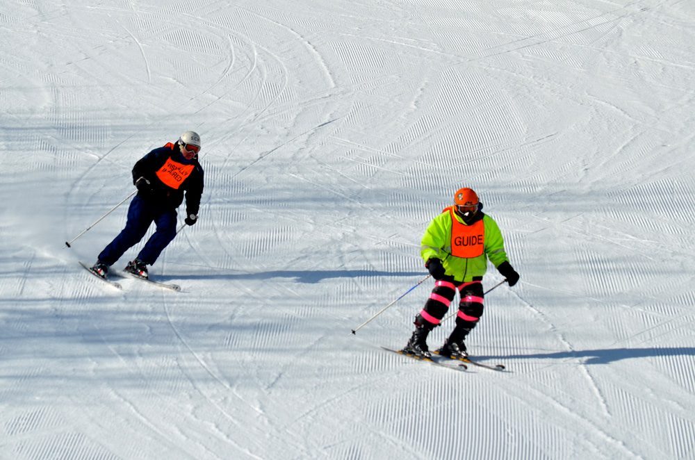 Tony Carleton, right, guided his friend, Dick Perkins, down the slopes at Wachusett Mountain Ski Area in Princeton, Mass., in 2016. Like other ski resorts in the state, Wachusett has relied on artificial snow this season. (Sharon Brody/WBUR)