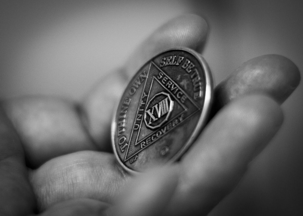 A man holds a chip AA members receive to mark sobriety. (Bernardo Fuller/Flickr)
