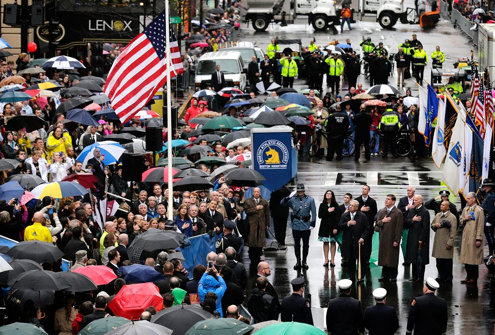 urvivors, officials, first responders and guests pause as the flag is raised at the finish line during a tribute in honor of the one year anniversary of the Boston Marathon bombings. (Charles Krupa/AP