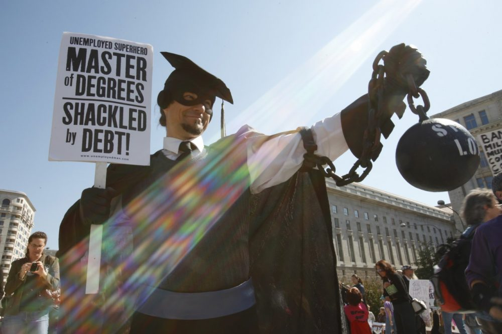 "In this Oct. 6, 2011 photo, Gan Golan, of Los Angeles, dressed as the ""Master of Degrees,"" holds a ball and chain representing his college loan debt, during Occupy DC activities in Washington. As President Obama prepared to announce new measures Wednesday to help ease the burden of student loan debt, new figures painted a demoralizing picture of college costs for students and parents: Average in-state tuition and fees at four-year public colleges rose an additional $631 this fall, or 8.3 percent, compared with a year ago. (AP)"