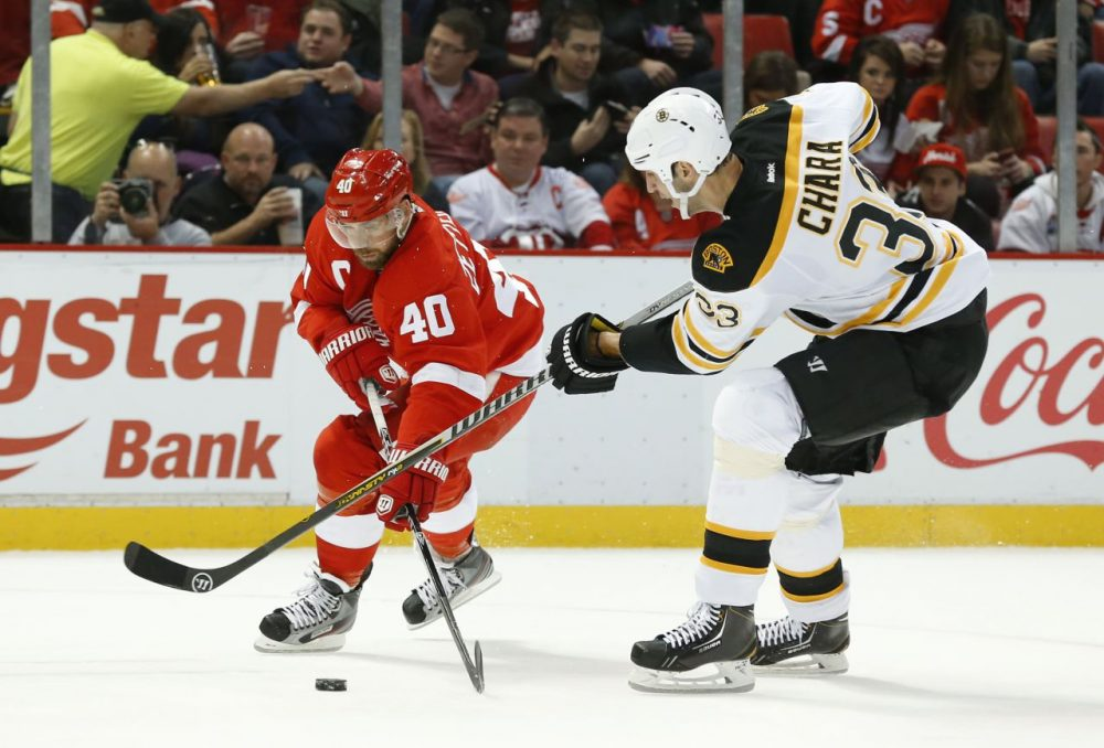 Detroit Red Wings left wing Henrik Zetterberg (40), of Sweden, and Boston Bruins defenseman Zdeno Chara (33), of the Czech Republic, battle for the puck in the second period of an NHL hockey game in Detroit Wednesday, Nov. 27, 2013. (Paul Sancya/AP)