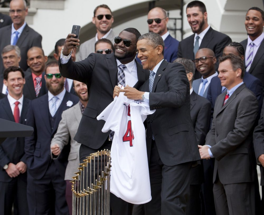 "Boston Red Sox designated hitter David ""Big Papi"" Ortiz, left, takes a selfie with President Barack Obama, holding a Boston Red Sox jersey presented to the president during a ceremony on the South Lawn of the White House in Washington, Tuesday, April 1, 2014, where the president honored the 2013 World Series baseball champion Boston Red Sox. (AP)"