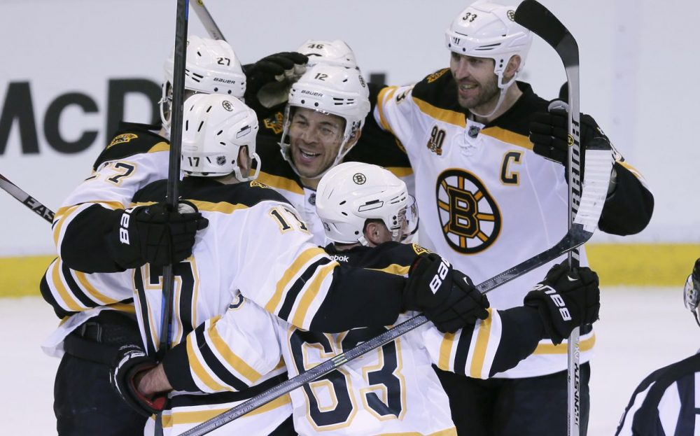 Boston Bruins right wing Jarome Iginla, center, is mobbed by teammates as they celebrate their 3-2 overtime win in Game 4 of a first-round NHL hockey playoff series against the Detroit Red Wings in Detroit, Thursday, April 24, 2014. Iginla was credited with the winning goal. (Carlos Osorio/AP)