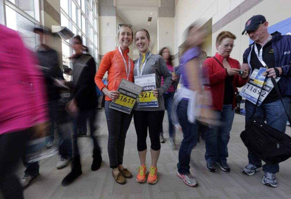 Cousins Laura Snebold, left, of Washington, and Christine Kenney, of Dedham, Mass., display their bibs to run in Monday's 118th Boston Marathon after picking them up Saturday, April 19, 2014, in Boston. (Robert F. Bukaty/AP)