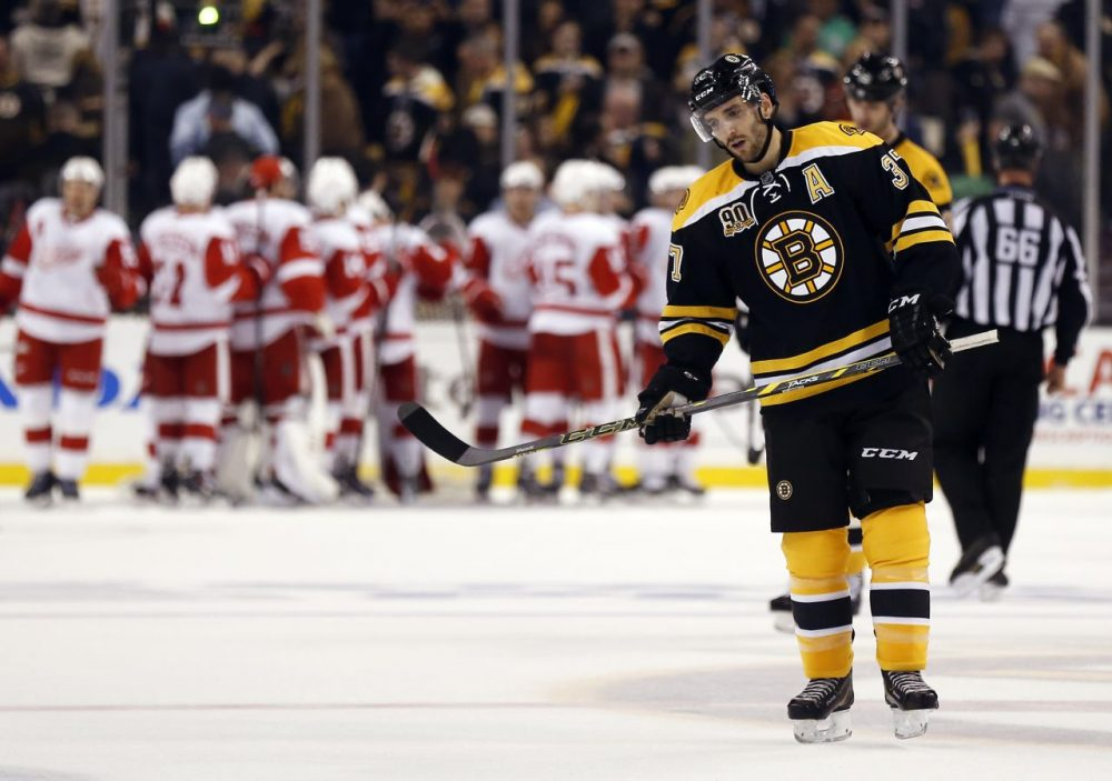 Bruins' Patrice Bergeron skates off the ice as the Detroit Red Wings celebrate their 1-0 win in Game 1 of a first-round NHL playoff hockey series, in Boston on Friday. (Winslow Townson/AP)