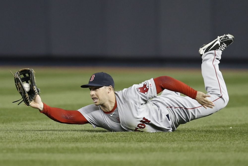 Boston Red Sox right fielder Daniel Nava shows the ball to the umpire after making a sliding catch on a third-inning fly-out hit by New York Yankees' Yangervis Solarte in a baseball game at Yankee Stadium in New York, Thursday, April 10, 2014. (Kathy Willens/AP)
