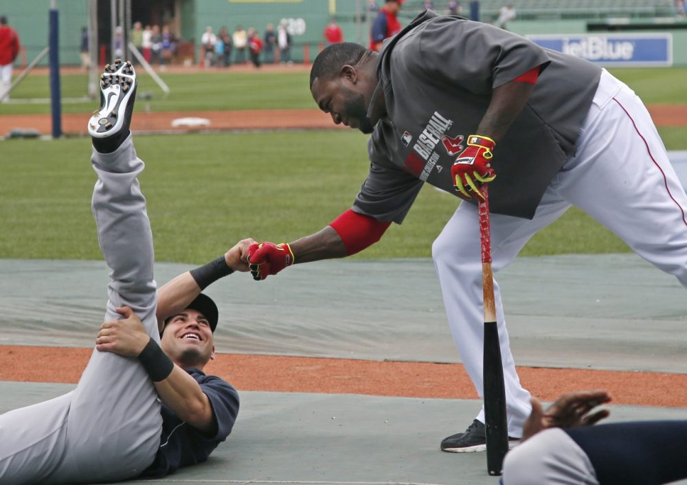 Boston Red Sox's David Ortiz, right, reaches down to greet a former teammate, New York Yankees' Jacoby Ellsbury, prior to a baseball game at Fenway Park in Boston, Tuesday, April 22, 2014. (AP)