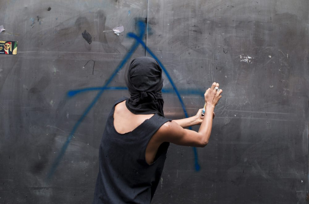 A young man spray paints an anarchist symbol on a kiosk during a march by anarchists on Labor Day in Mexico City, Thursday, May 1, 2014. Thousands of people, many calling for greater worker rights and protections, participated in various marches around the city center. (Rebecca Blackwell/AP)