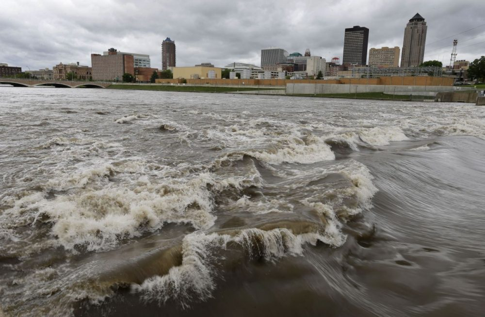 """Water splashes over the Center Street Dam in the swollen Des Moines River in downtown Des Moines, Iowa. Climate change's assorted harms """"are expected to become increasingly disruptive across the nation throughout this century and beyond,"""" the National Climate Assessment concluded Tuesday. (Charlie Neibergall/AP)"""