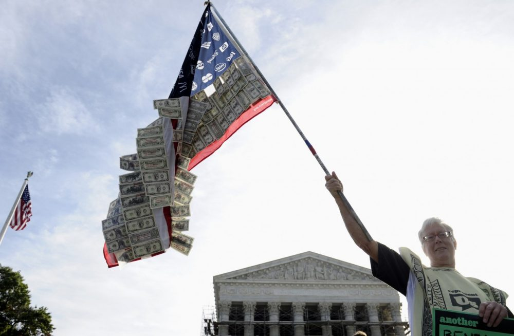 David Barrows of Washington holds a flag covered in money and corporate logos during a demonstration outside. (Susan Walsh/AP)