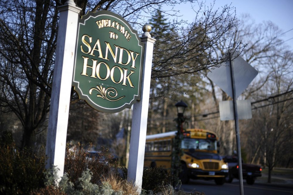 A bus drives past a sign reading Welcome to Sandy Hook Dec. 4, 2013, in Newtown, Conn. (Jessica Hill/AP)