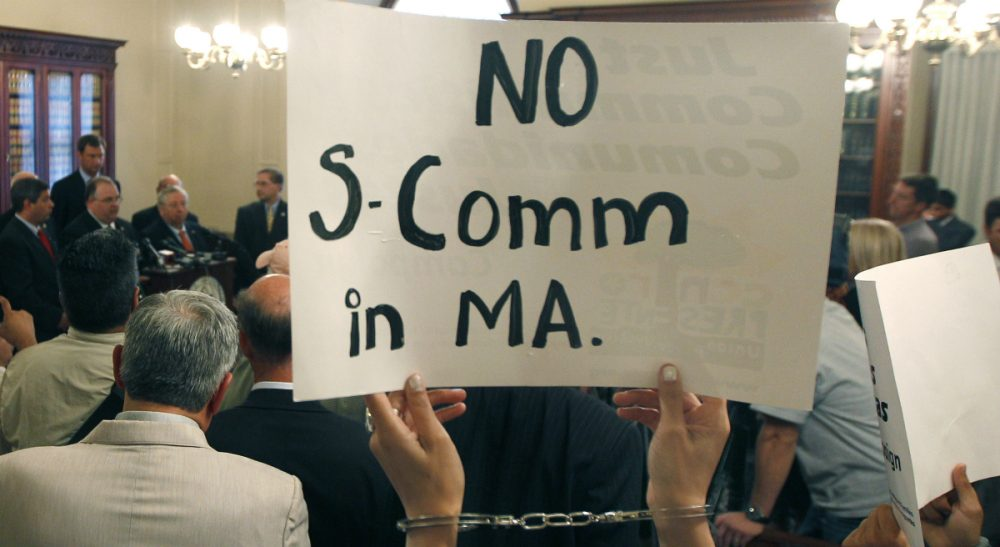 """In this file photo, protesters wearing handcuffs holds up signs urging the stop of the """"Secure Communities"""" program, or """"S Comm,"""" at a news conference held by Massachusetts county sheriffs at the Statehouse in Boston, Wednesday, Sept. 28, 2011. (Charles Krupa/AP)"""