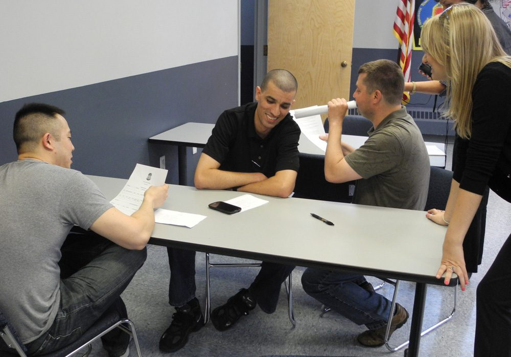 In a training exercise, Somerville Police Officer Eli Kim, left, tries to book Somerville Officer Samir Messaoudi -- playing the role of a man with schizophrenia -- while Cambridge Police Officer Fred Cabral does the sound effects of voices in Messaoudi's head. (Cambridge Police Department)