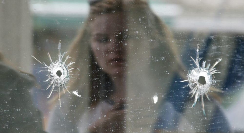 A woman looks at the bullet holes on the window of IV Deli Mark where Friday night's mass shooting took place by a drive-by shooter on Saturday, May 24, 2014, in Isla Vista, Calif. (Jae C. Hong/AP)