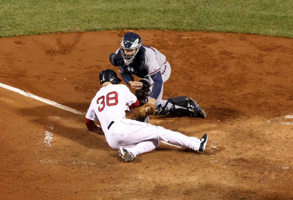 Atlanta Braves catcher Evan Gattis puts the tag on Boston Red Sox's Grady Sizemore (38) who is out trying to score on a fielder's choice in the sixth inning of a baseball game. (AP/Elise Amendola)