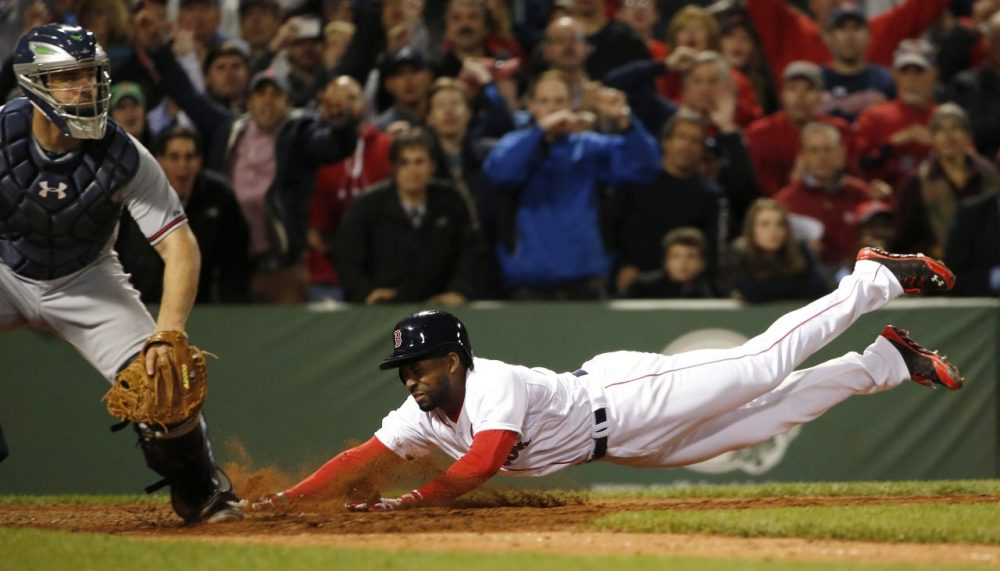 Boston Red Sox's Jackie Bradley Jr. dives home with the game-winning run on an infield single by teammate Xander Bogaerts as catcher Evan Gattis, left, looks on during the ninth inning. (AP/Winslow Townson)