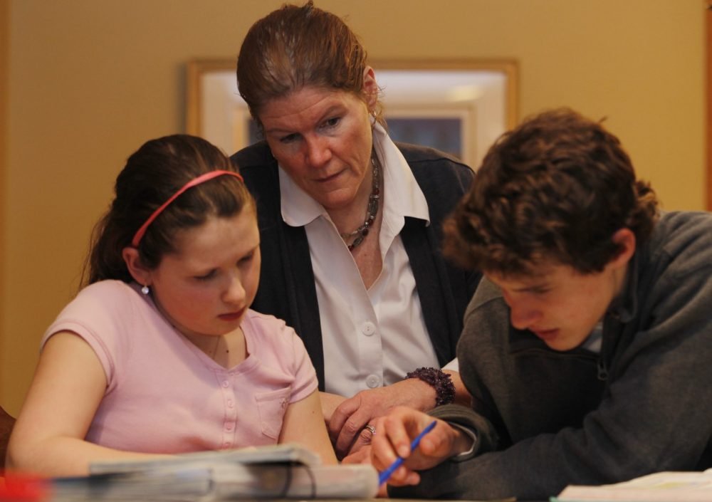 Ellen Purtell, center, watches her 15-year-old son Bobby Costanzo, right, help his sister Grace Costanzo, 10, with homework. (Julio Cortez/AP)
