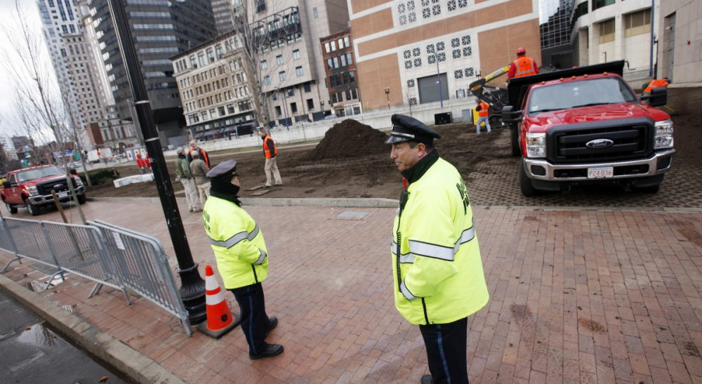 Work crews bring in new top soil behind a police barricade at the site of the Occupy Boston encampment in Dewey Square in Boston, Saturday, Dec. 10, 2011. More than 40 people were peacefully arrested as the park was cleared by police. (Michael Dwyer/AP)