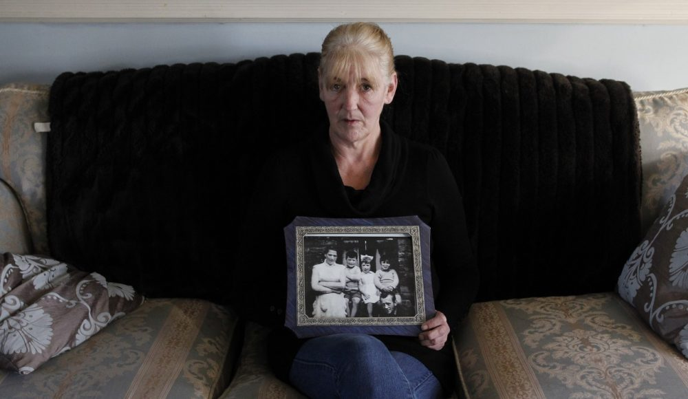 In this Thursday, Jan. 12, 2012 file photo, Helen McKendry holds a family photograph showing her mother Jean McConville at home in Killyleagh, Northern Ireland. Northern Ireland police say they have charged a 77-year-old man with involvement in the Irish Republican Army's 1972 abduction, killing and secret burial of a Belfast woman, an unsolved case linked to Sinn Fein leader Gerry Adams. The man was scheduled to be arraigned Saturday on charges of IRA membership and aiding the killers of Jean McConville, a widowed mother of 10. The IRA accused the 38-year-old of spying for British forces, abducted her at gunpoint from her home, and shot her in the back of the head. The IRA admitted responsibility in 1999. Her unmarked grave was discovered four years later in the Republic of Ireland. Two former IRA members since have accused Adams, a senior Belfast IRA figure in 1972, of ordering McConville's execution. Adams denies any involvement. (AP)