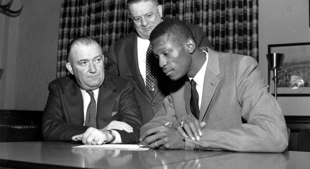 Basketball player Bill Russell, right, signs the contract with the Boston Celtics of the National Basketball Association at Boston Garden in Boston, Mass., on Dec. 19, 1956. Seated at left is Celtics co-owner and president Walter Brown, and standing behind him is co-owner Lou Pieri. Thomas J. Whalen says Brown blazed an integrationist path that transformed the NBA. (AP)