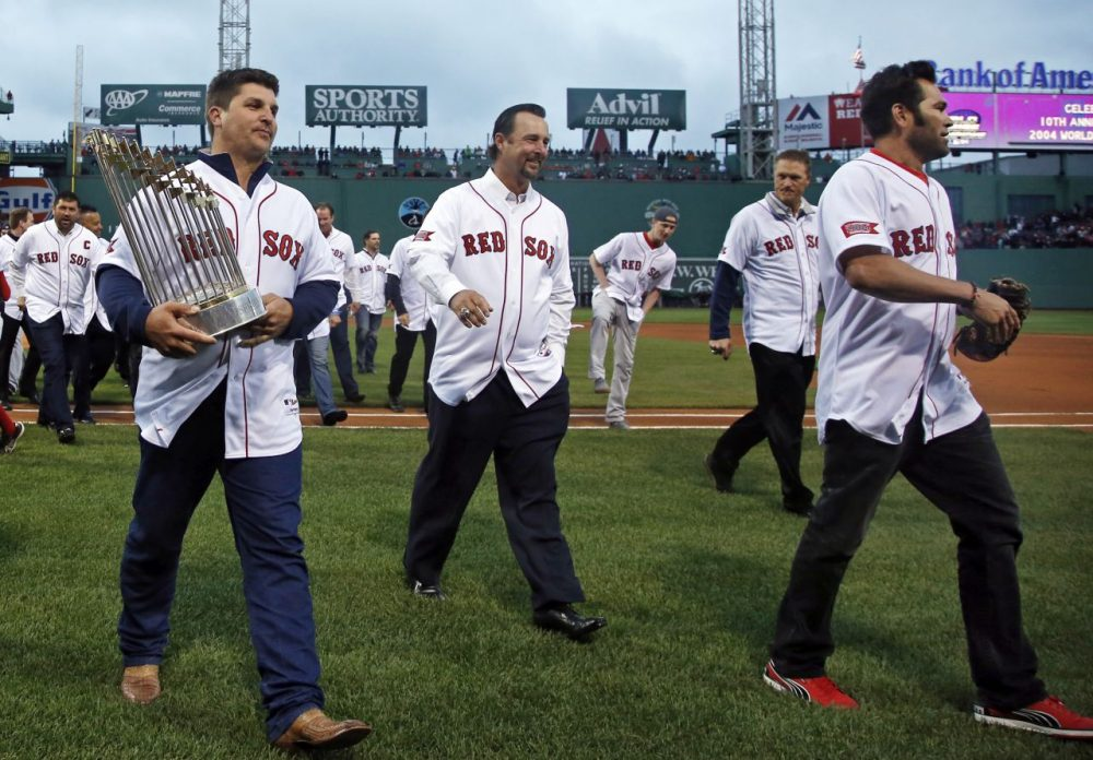 Former Boston Red Sox pitcher Keith Foulke, left, carries the 2004 World Series trophy walking off the field with 2004 teammates, Tim Wakefield, middle, and Johnny Damon, right, after they were honored at Fenway Park prior to a baseball game against the Atlanta Braves in Boston, Wednesday, May 28, 2014. (Elise Amendola/AP)