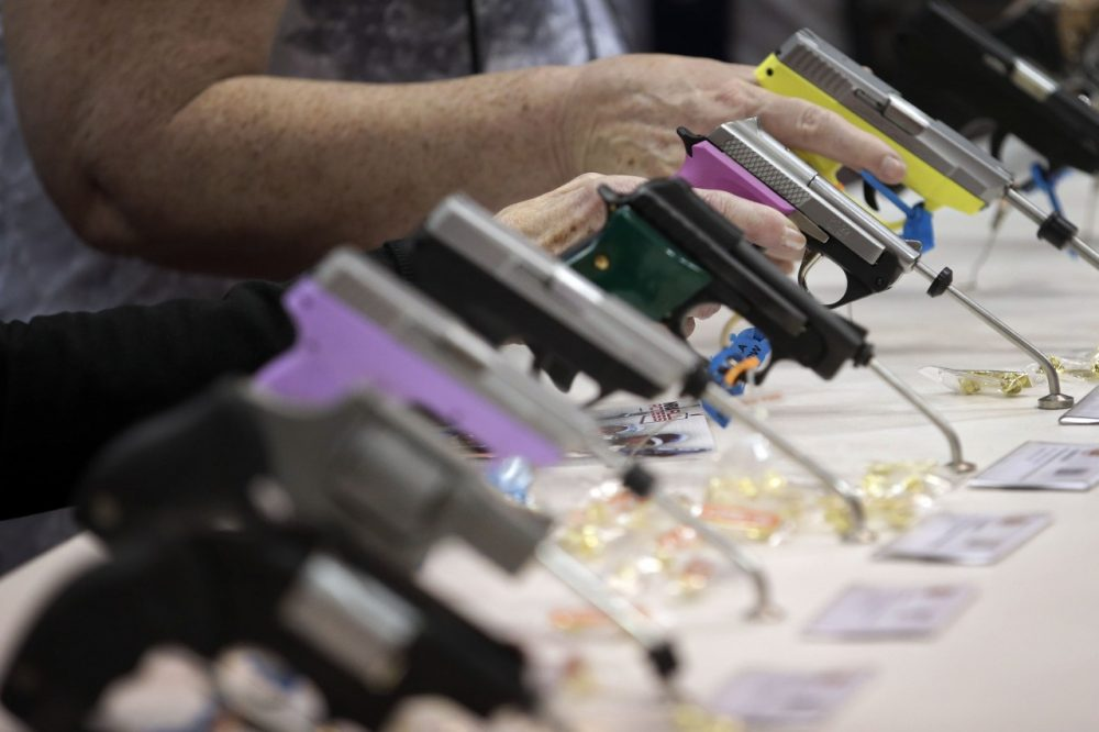 Attendees look over a pistol display at the National Rifle Association's annual convention in Friday, April 25, 2014 in Indianapolis. (AP)