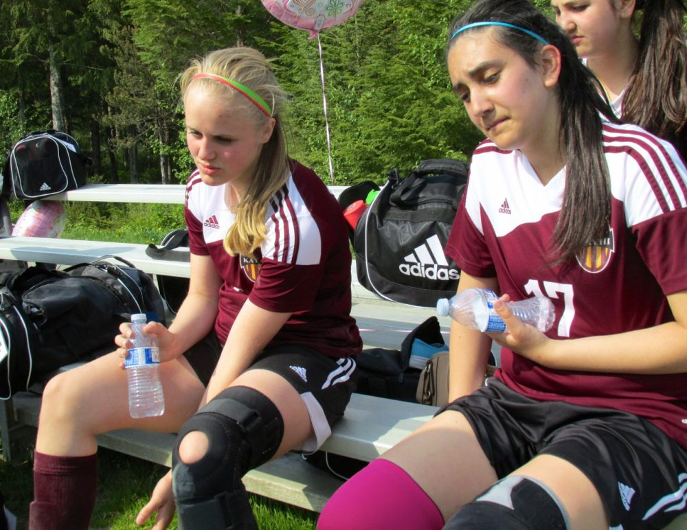 Angel Spurgeon and Vonni Spigai rest during halftime in their first game against Sitka. (Emily Files)