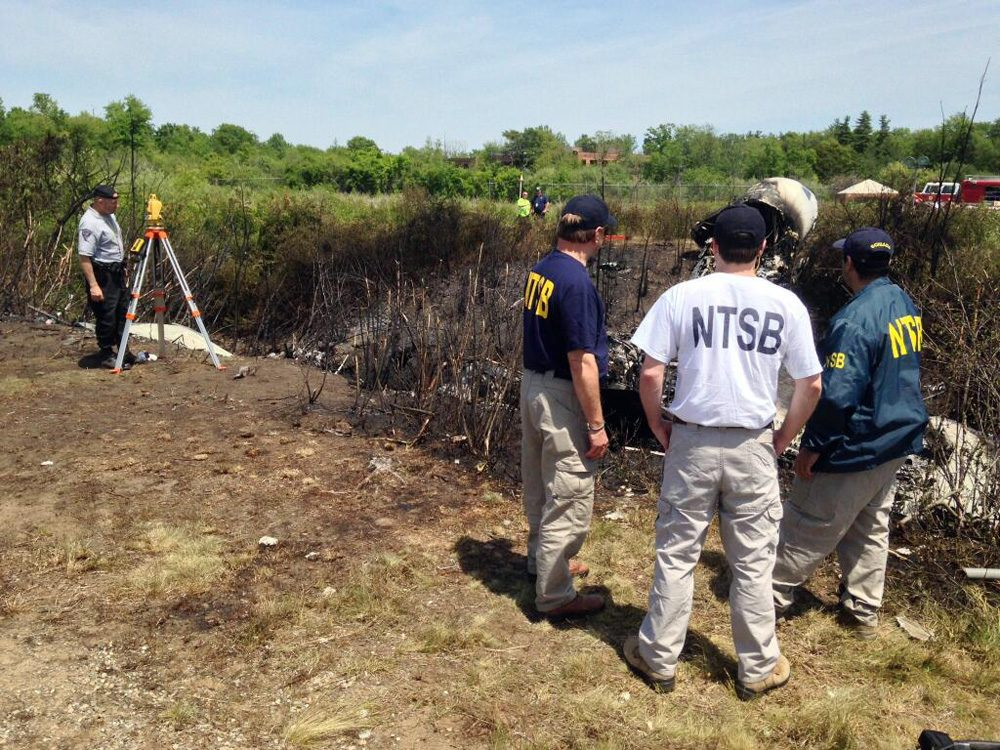 NTSB investigators on Sunday are at the scene of a private plane that plunged down an embankment and erupted in flames during a takeoff attempt Saturday night at Hanscom Field in Bedford. (National Transportation Safety Board/AP)