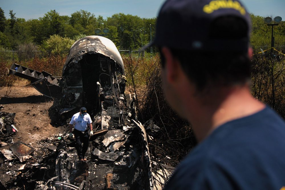 Wreckage lay at the scene Monday in Bedford,  where a private plane plunged down an embankment and erupted in flames during a takeoff attempt at Hanscom Field Saturday night. Seven people died in the crash.  (Fred Thys/WBUR)